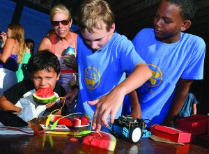 "Jacob Long, 12, of Newport, center, and Nick Lockhart, 12, of Newport, right, demonstrate their ""maker"" prowess as Willy Mejia, 5, of Newport bites into a piece of watermelon that sends a signal to a 'makey-makey' board and onto a second piece of watermelon ultimately making the blue robot move during the FabNewport Maker Party on Sunday at the Casino Theatre in Newport. Courtesy Newport Daily News"